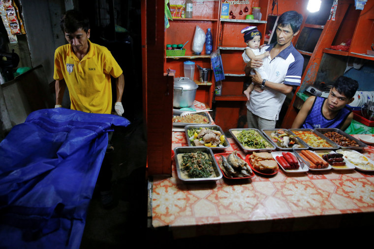 Image: A food vendor holds a baby as funeral workers carry the body of one of two men killed inside a slum in port area on Manila