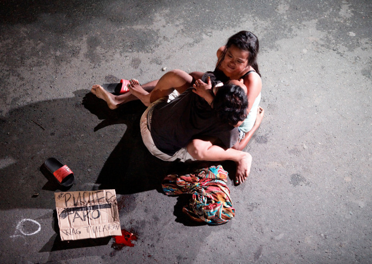 Image: A woman cradles the body of her husband, who was killed on a street by a vigilante group, according to police, in a spate of drug related killings in Pasay city, Metro Manila