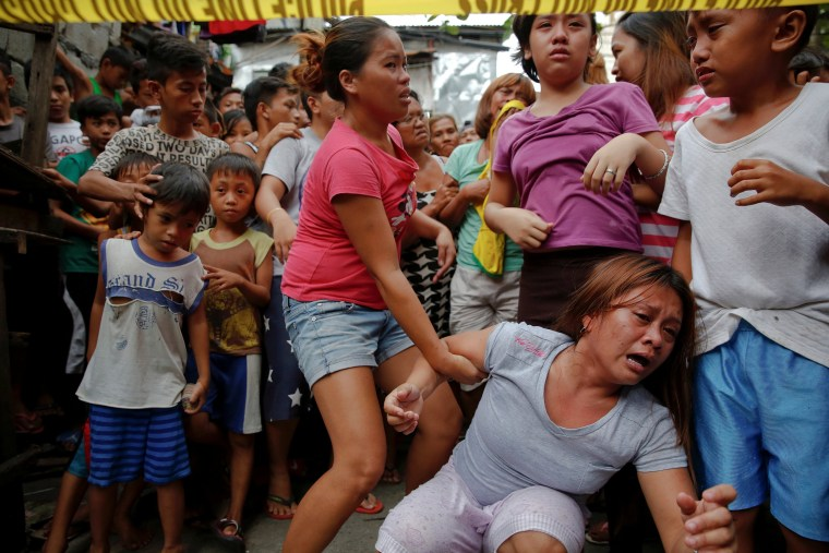 Image: Janeth Mejos reacts as the body of her father Paquito Mejos is taken out of their home shortly after he was killed in a police operation in Manila