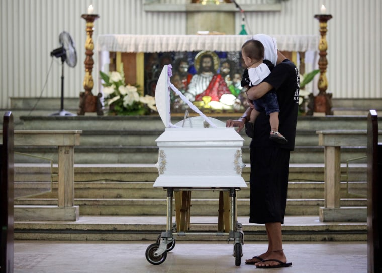 Image: A relative carries the son of Eric Quintinita Sison during burial rites in Pasay city