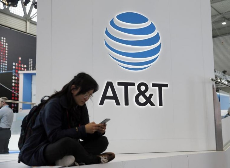 A woman looks at her mobile next to AT&T logo during the Mobile World Congress in Barcelona