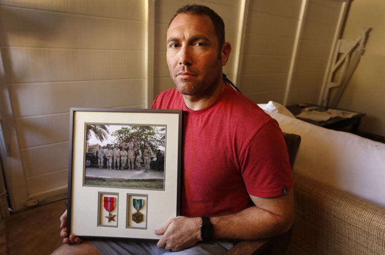Robert D'Andrea, an Iraq war veteran who served with the U.S. Army and the California National Guard, holds a frame with a photo of his team on his first deployment to Iraq in his home in Los Angeles.
