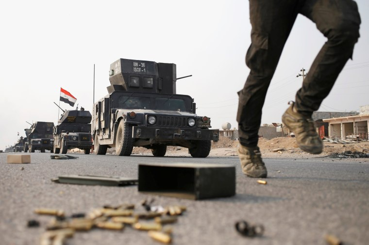 Image: An Iraqi special forces soldier runs as other drive in armoured vehicles on a road near Mosul