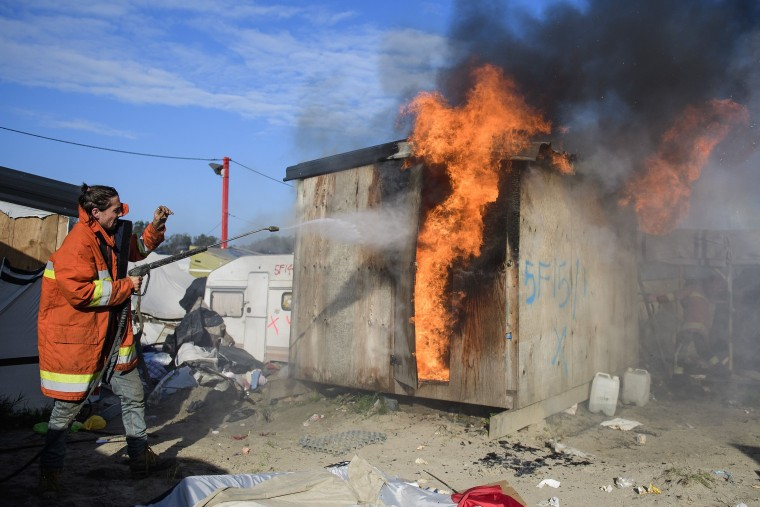 Image: A shelter set alight inside the migrant and refugee camp in Calais, known as the 'Jungle'. Photo by Ben Cawthra/REX/Shutterstock
