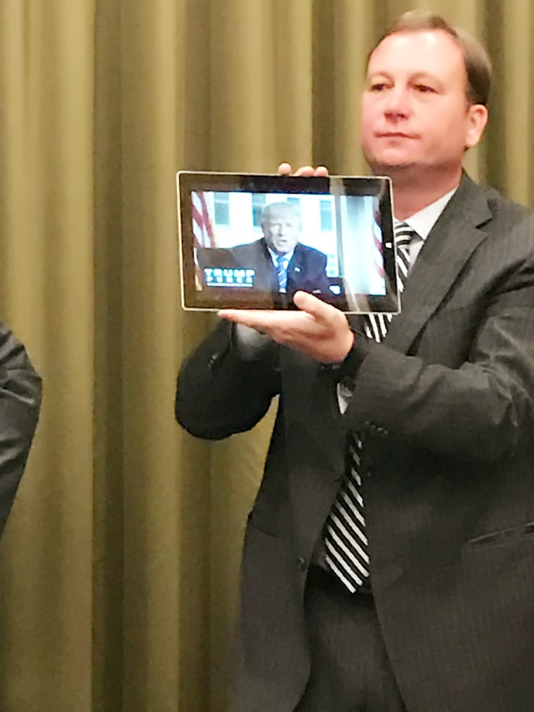 Trump campaign director of coalitions Alan Cobb holding a tablet showing a welcome video featuring Donald Trump at an Asian Pacific American advisory meeting in Nevada ahead of the third presidential debate.