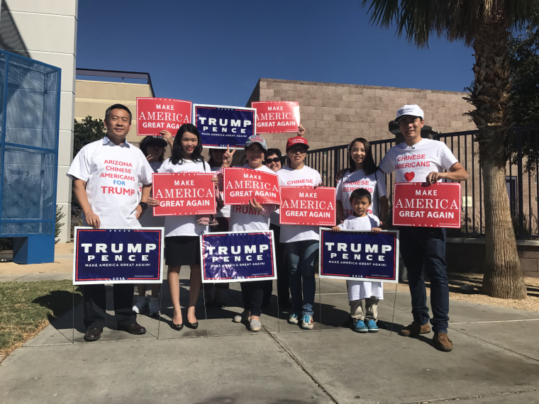Volunteers with Chinese Americans for Trump with signs.