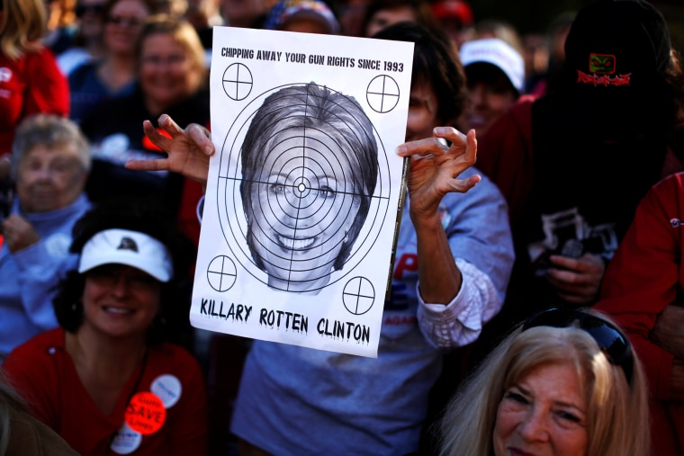Image: A supporter of Republican U.S. presidential nominee Donald Trump holds a shooting target with image of Hillary Clinton at a campaign rally in Virginia Beach