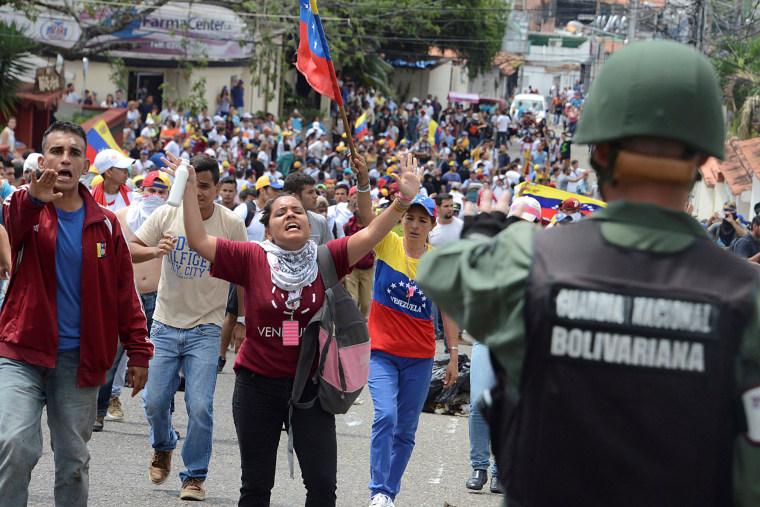 Image: Demonstrators shout slogans in front of Venezuelan National Guard members during a rally demanding a referendum to remove Venezuela's President Maduro in San Cristobal