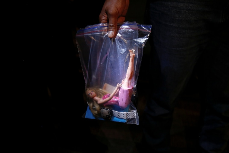 Image: A policeman holds a bag with bloodied doll and other belongings of a 17 year old girl that was killed together with her friend by unknown motorcycle-riding gunmen, in an alley in Manila