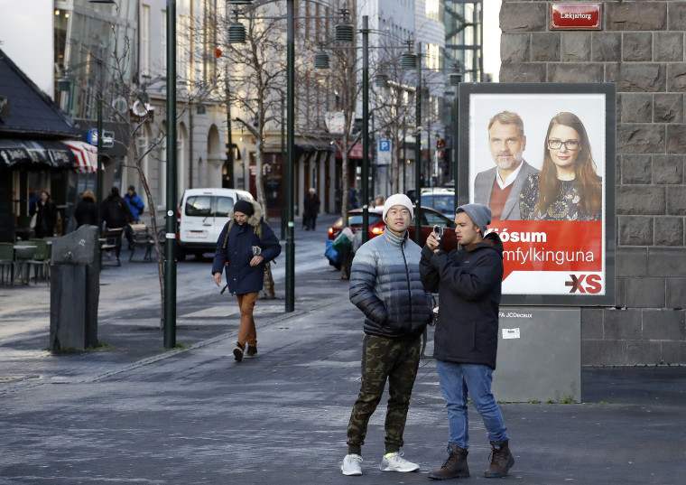 Image: People walk past an social democrats election poster in Reykjavik