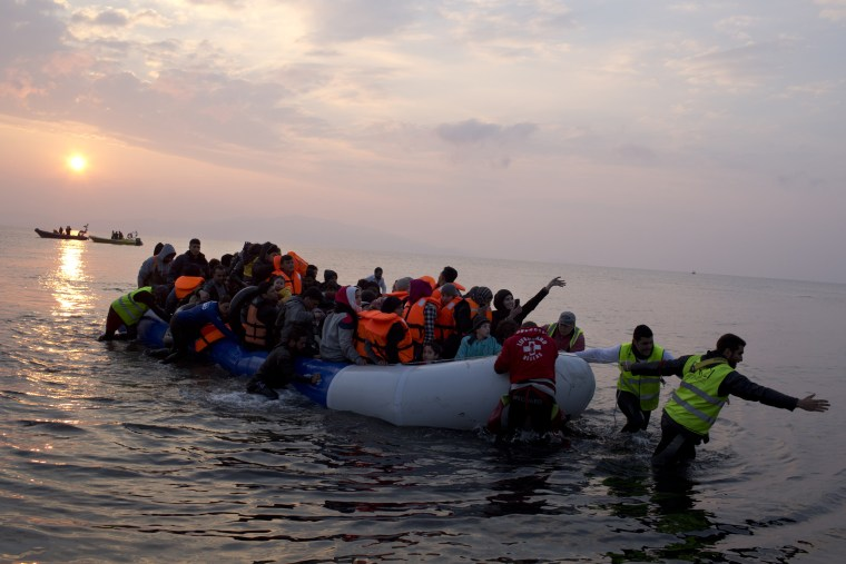 Image: Volunteers help migrants and refugees on a dingy as they arrive at the shore of the northeastern Greek island of Lesbos