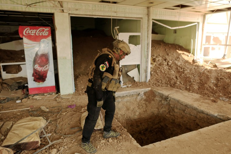 Image: An Iraqi special forces soldier looks inside the entrance of a tunnel used by Islamic State militants inside a restaurant in Bazwaia, east of Mosul