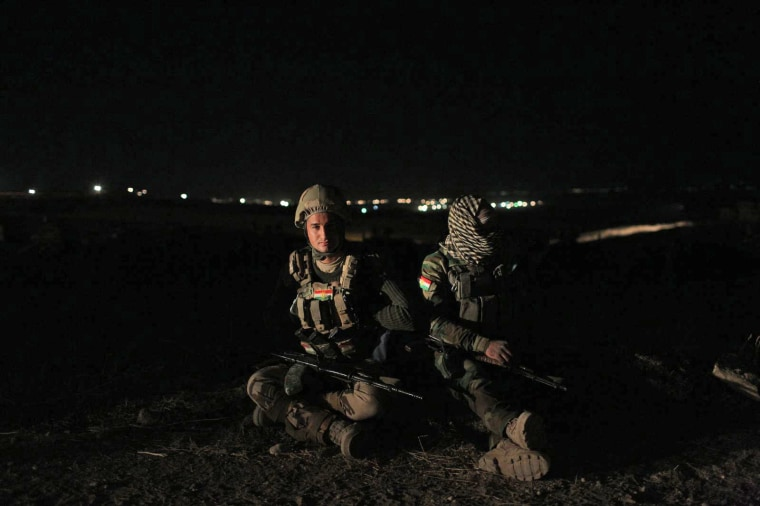 Kurdish Peshmerga soldiers on the night before the offensive.