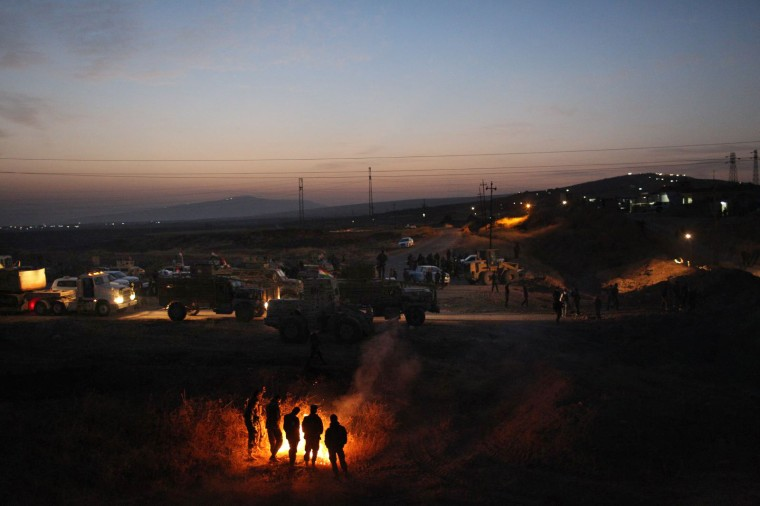 Kurdish Peshmerga and Iraqi army soldiers wait to cross the front line on Oct. 20.