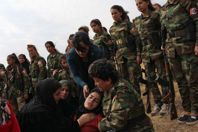 """The sister of Awara, the slain PAK soldier, is held by other mourners during her brother's funeral in the mountains near Irbil, Iraq, on Oct. 26. Awara's sister came from Iran for the funeral. \""""Many soldiers took a break from the front line to attend [the funeral] but there were still 200 others who remained and continued fighting. The unit and Awara's fellow soldiers asked me to honor his death by sharing the story.\"""""""