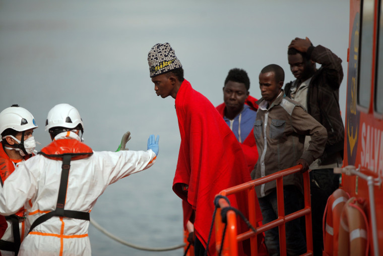 Image: A migrant, who is part of a group intercepted aboard a dinghy off the coast in the Mediterranean sea, is stopped after arriving on a rescue boat at a port in Malaga