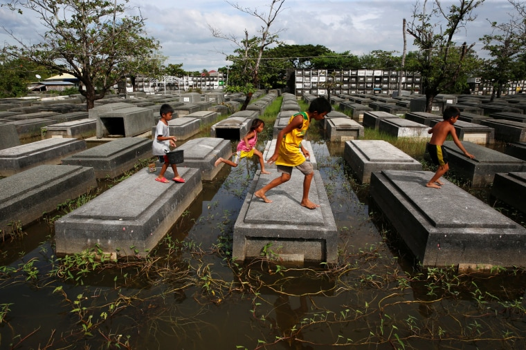 Image: Residents who work at a cemetery to refurbish the tombs ahead of the commemoration of All Saints Day, walk between the tombs in a flooded cemetery at Masantol, Pampanga