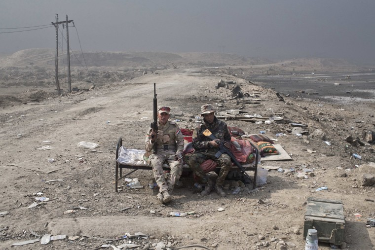 Image: Iraqi army soldiers rest at a checkpoint in Qayara