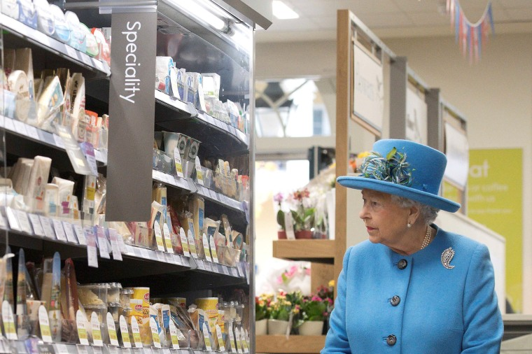 Image: Britain's Queen Elizabeth looks at products on the shelves at a Waitrose supermarket during a visit  to the town of Poundbury