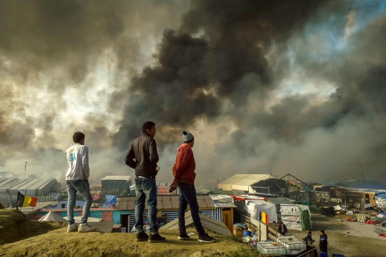 """Image: Migrants stand on a hill overlooking the """"Jungle"""" migrant camp in Calais"""