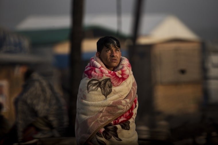 Image: A migrant looks up to the sky as he stands next to his burnt tent in the migrant camp