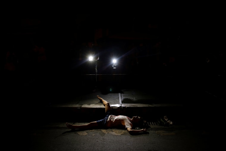 Image: The body of a man killed by unknown gunmen is lit by lights from TV cameras in Manila