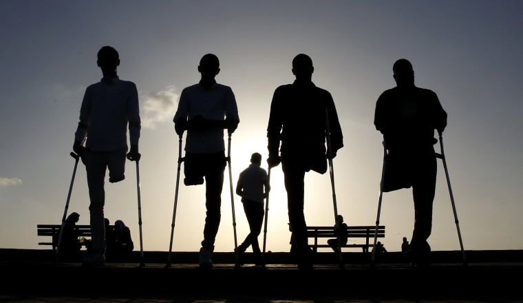 Image: Four Palestinian friends who were injured during conflicts walk by the sea at Gaza's small fishing harbor