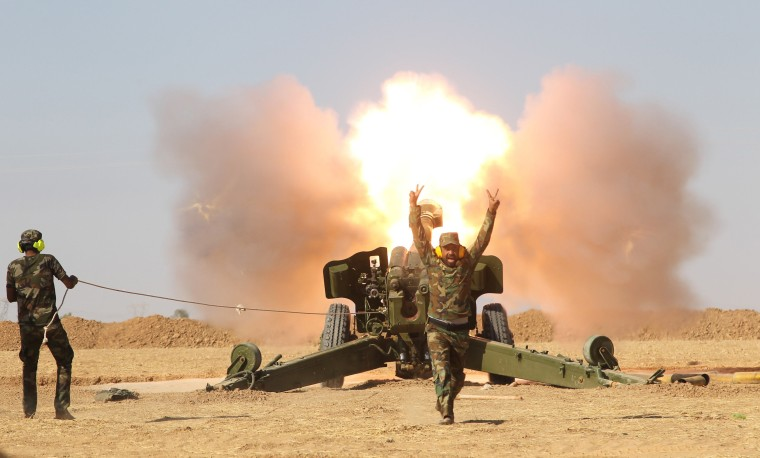 Image: Popular Mobilization Forces (PMF) personnel fire artillery during clashes with Islamic State militants south of Mosul