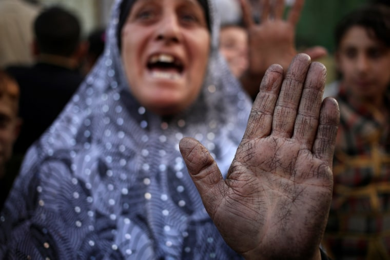 Image: A displaced woman complains about what she says is a lack of food supplies, while her hand is covered by a layer of grime from an oil facility that Islamic State torched, in Qayyara