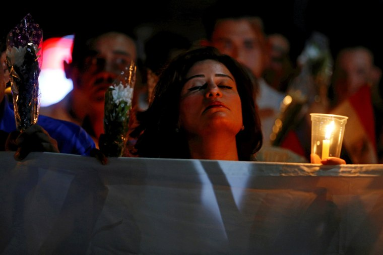 """Image: A woman reacts while marching with candles to the \""""Peace Square\"""" during a ceremony to mark the first anniversary of the Russian MetroJet plane crash in the Red Sea resort of Sharm el-Sheikh"""