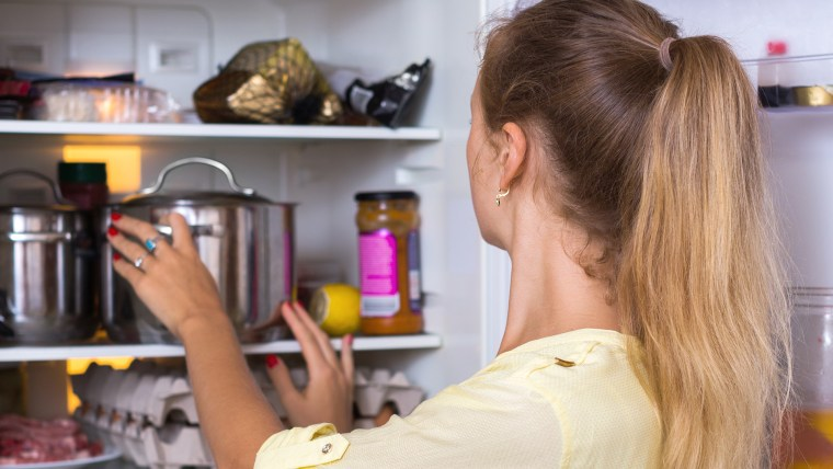 woman standing in front of open fridge
