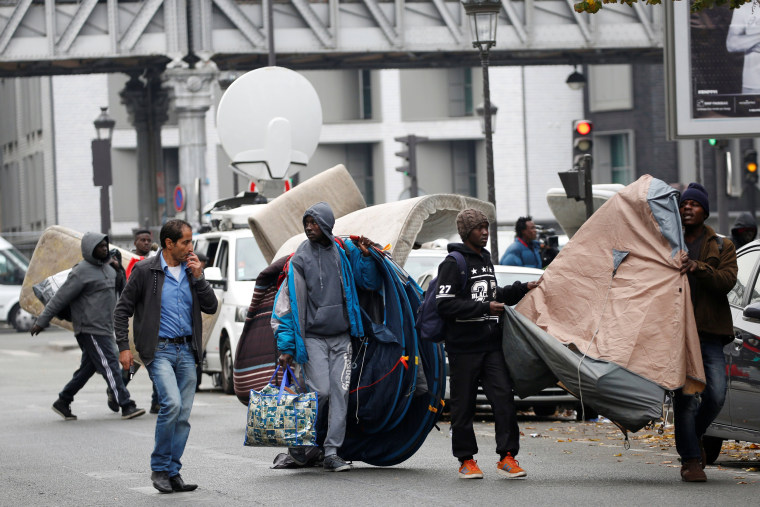 Image: Migrants move tents from a makeshift camp in a street near Stalingrad metro station in Paris
