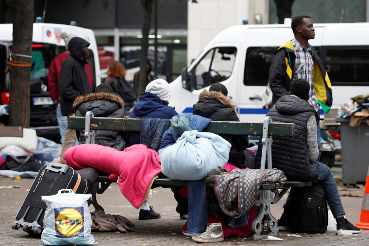 Image: Migrants sit on a bench at a makeshift camp on a street near Stalingrad metro station in Paris