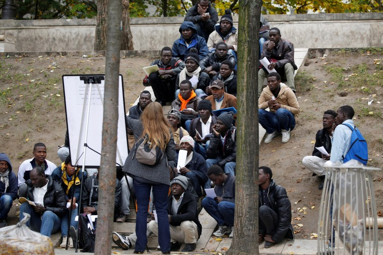 Image: Migrants attend a French lesson near their makeshift camp in Paris, France