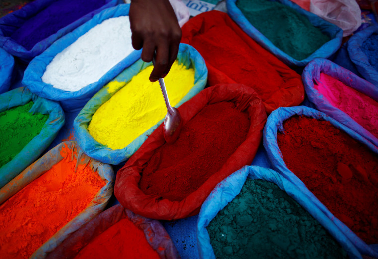 Image: A street vendor spreads vermilion powder used for worship during the Tihar festival, also called Diwali, in Kathmandu