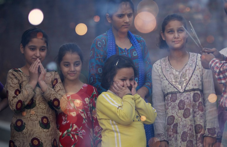Image: Children watch firecrackers being lit on the eve of Diwali