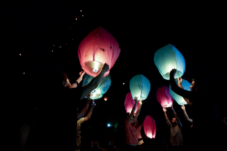 Image: People hold sky lanterns to release during a campaign against the use of firecrackers during Diwali