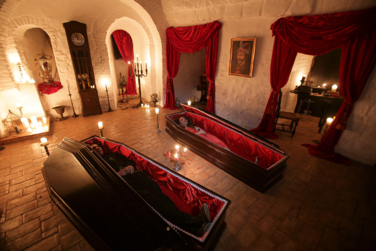 Image: Tami and Robin Varma lie in red velvet-trimmed coffins