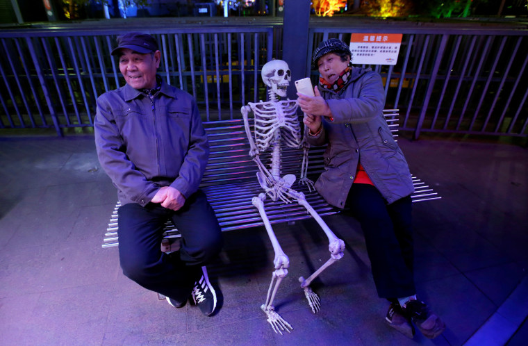Image: A woman takes a selfie with a fake skeleton next to her husband ahead of a Halloween parade in Beijing