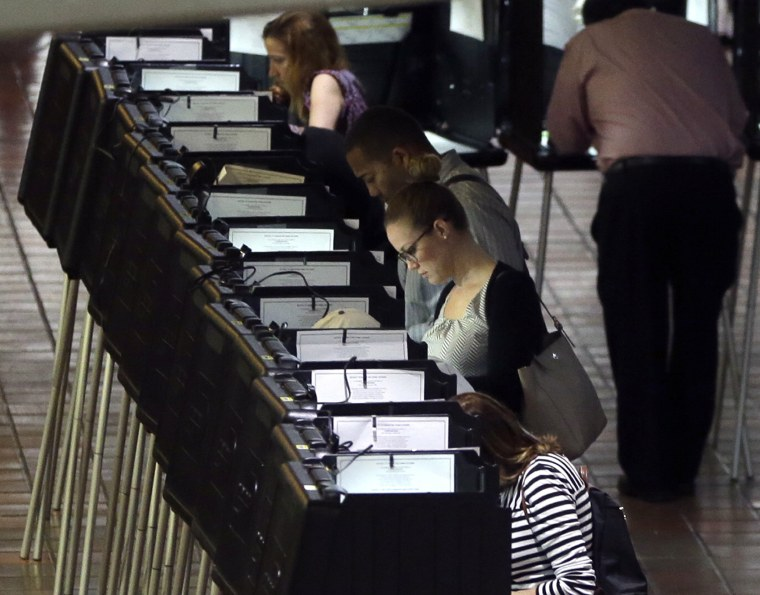 Image: People vote at a polling station on the first day of early voting in Miami-Dade County