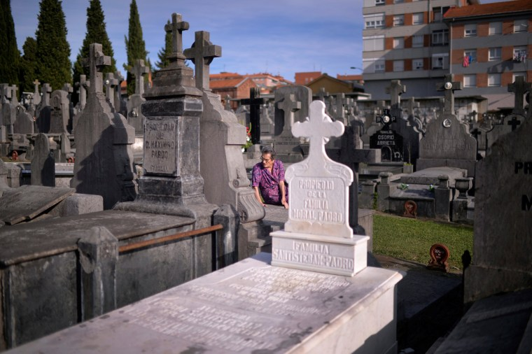 Image: A woman sits on a grave on All Saints' Day at Derio cemetery near Bilbao