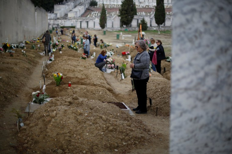 Image: A woman visits a grave during All Saints Day at Alto de Sao Joao cemetery in Lisbon