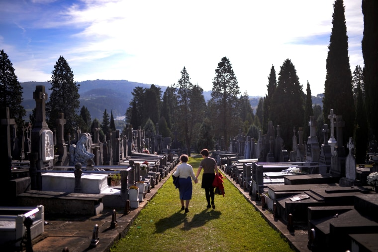 Image: Women walk past graves on All Saints' Day at Derio cemetery near Bilbao