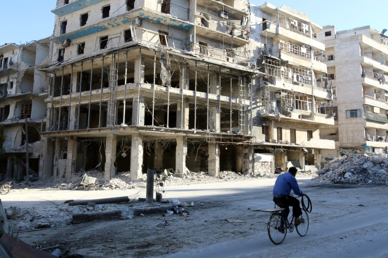 Image: A man rides a bicycle near damaged buildings in Aleppo on Oct. 19, 2016