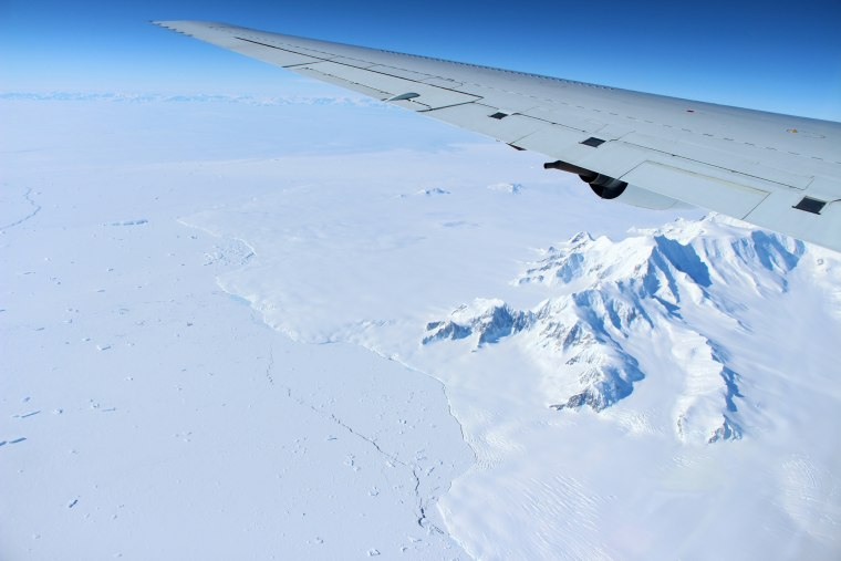 The mountains of northern Alexander Island in the Antarctic Peninsula pass under the wing of a DC-8 aircraft carrying Operation IceBridge?s scientists and instruments on Oct. 14.