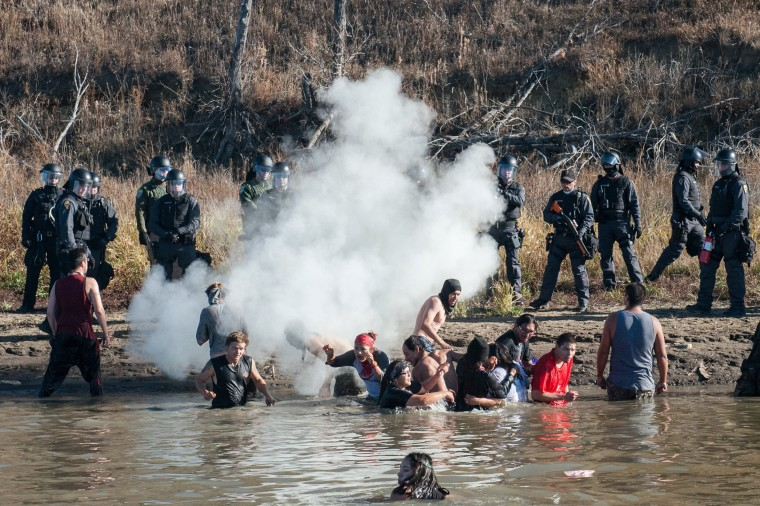 Image: Police officers use tear gas against protesters standing in the water during a protest against the building of a pipeline on the Standing Rock Indian Reservation near Cannonball, North Dakota