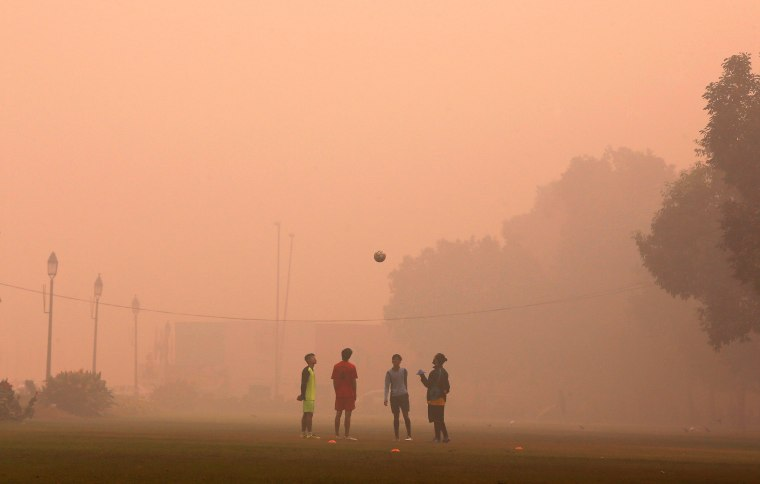 Image: Boys play football in a public park on a smoggy morning in New Delhi