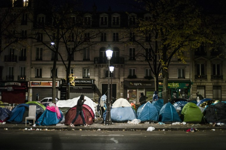 Image: A migrant passes by tents in a makeshift camp in the 19th district of Paris, Thursday.