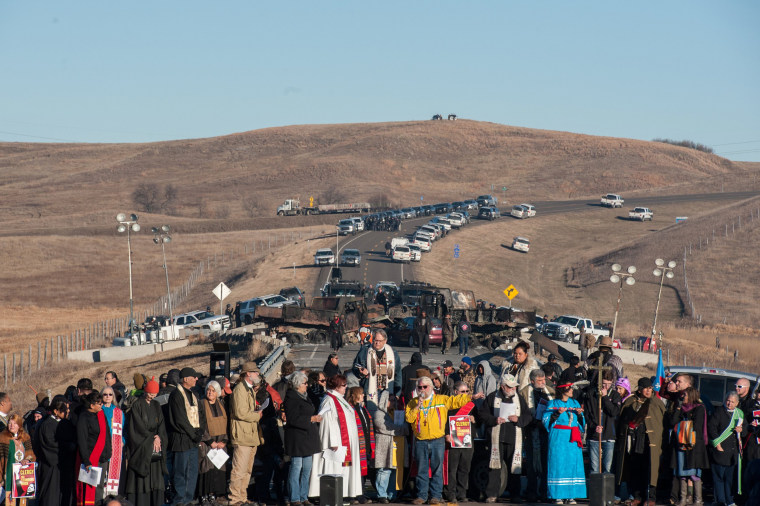 Image: Members of the clergy from across the United States participate in a prayer circle in front of a bridge where demonstrators are facing off against police during a protest of the Dakota Access pipeline on the Standing Rock Indian Reservation near Ca