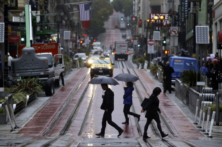 This Oct. 14, 2016 file photo shows pedestrians carrying umbrellas as they cross Powell Street and cable car tracks in San Francisco. Amid a wet start to California's rainy season, and some mending of Californians' backsliding ways on water conservation, the advice of the state's drought czar: Relax and enjoy the rain. For now. The board will release Californians' latest monthly water-use figures Tuesday, Nov. 1, 2016, under the state's nearly three-year drought emergency.